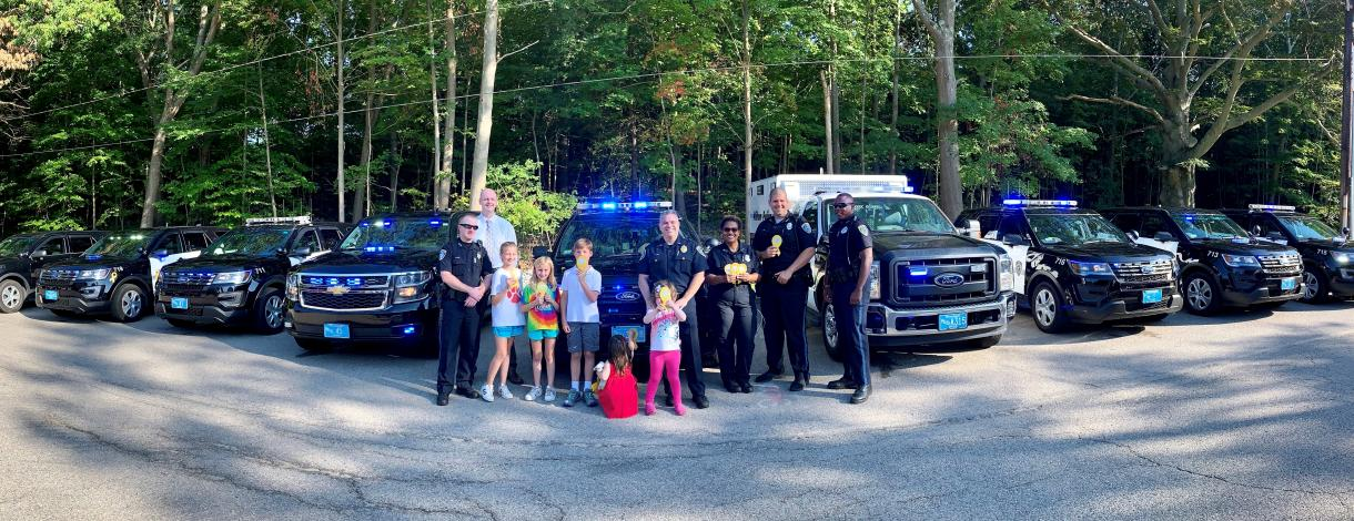 Image of Kids in front of Police Cruisers